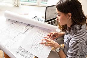 Berufshaftpflichtversicherung Architekten – Architektin untersucht Pläne