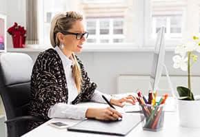 Berufshaftpflichtversicherung Designer – Designerin arbeitet am Tablet