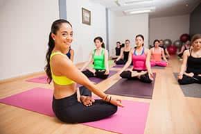 Berufshaftpflichtversicherung Yogalehrer – Yogalehrerin sitz vor ihrer Klasse