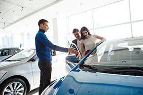 Betriebshaftpflichtversicherung Autohändler – Autohändler zeigt Kunden ein Auto