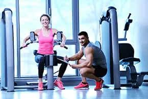 Betriebshaftpflichtversicherung Fitnesstrainer – Fitnesstrainer zeigt Kundin eine Übung