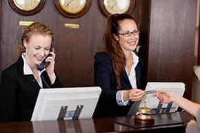 Betriebshaftpflichtversicherung Hotel – Empfangsdamen an der Rezeption width=