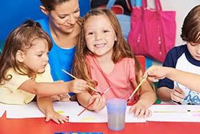 Betriebshaftpflichtversicherung Tagesmütter – Junge Frau malt mit Kindern