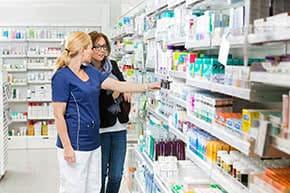 Betriebshaftpflichtversicherung für Apotheken – Apothekerin zeigt Kundin ein Medikament